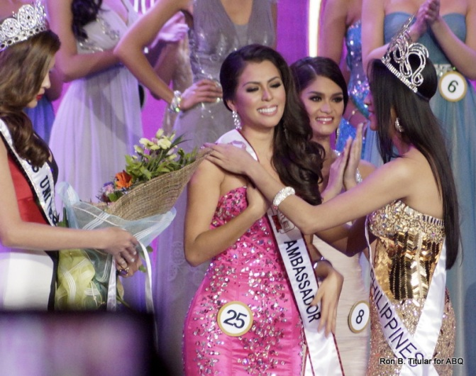 As Ariella Arida places the Smart Ambassadress sash on MJ, Gabriella Isler approaches the pair with the victory bouquet...